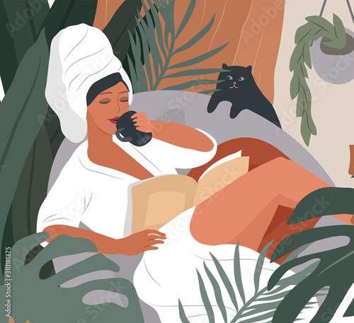 Obraz Happy cute girl with towel on head and in bathrobe, drinks coffeeor tea in morning after bathing, read the newspaper and resting with cat. Feminine Daily life by young woman with - fototapety do salonu