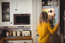 Woman Looking For Food In Refrigerator In Kitchen