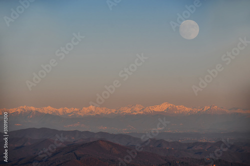 Obraz Il tramonto sulla catena di montagne con la luna piena - fototapety do salonu