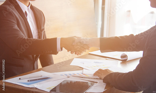 Photo  Two confident business man shaking hands during a meeting in the office, success