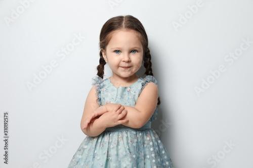 Valokuvatapetti Cute little girl on light grey background