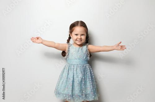Fotografiet  Cute little girl on light grey background