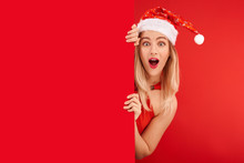 Shocked Surprised Girl In Santa Claus Hat Isolated On Festive Red Background With Copy Space, Time To Buy Gifts For Christmas And New Year, Discounts And Sale