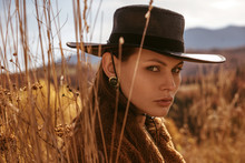 Outdoor Close Up Fashion Portrait Of Young Beautiful Confident Brunette Woman With Natural Freckled Skin Wearing Stylish Black Wide Brimmed Hat, Earrings, Faux Fur Coat, Posing In Mountain Landscape