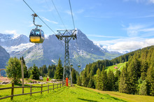 Yellow Cable Car In The Swiss Alps. Gondola Going From Grindelwald To First In The Jungfrau Area. Summer Alpine Landscape With Snowcapped Mountains In The Background. Transport Tourists Uphill