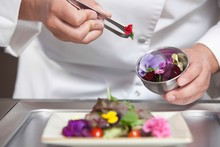 Chef Arranging Edible Flowers On Salad