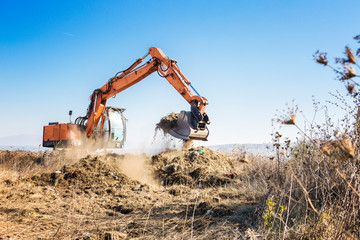 Excavator clears land for construction of a highway