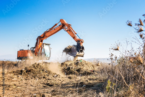 Fotomural Excavator clears land for construction of a highway