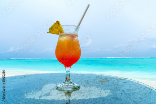 Glass of cocktail is on sandy coral beach, Maldives, The Indian