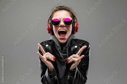 smiling impudent girl listens to music in red headphones on a gray background - 310218376