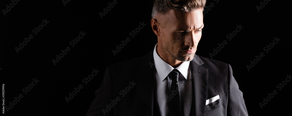 Fototapeta Panoramic shot of handsome businessman looking away isolated on black