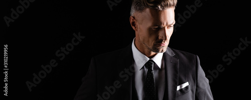 Obraz Panoramic shot of handsome businessman looking away isolated on black - fototapety do salonu