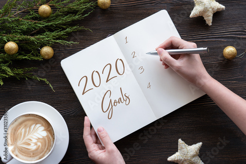 Photo  Female hands write 2020 new year resolution goal wish list in notebook on brown