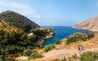 Beautiful aerial view of hiker couple look to distance. mountains and sea on sun rise. Trail for active sports, hiking to a wild beach, tourist destination. Ieranto bay, Nerano, Massa Lubrense, Italy