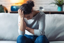 Depressed Young Woman Thinking About Her Problems While Sitting On The Sofa At Home.