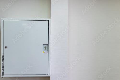 Fototapeta Fire hose in a metal box on the wall obraz na płótnie