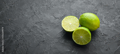 Valokuva Green sliced lime on black stone background