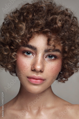 Portrait of young beautiful freckled girl with curly hair and clean makeup Fototapet