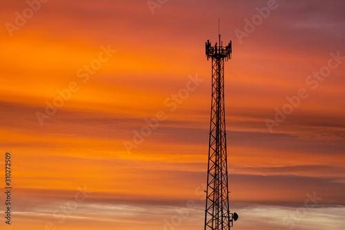 background communication tower at an orange sunrise Fotobehang