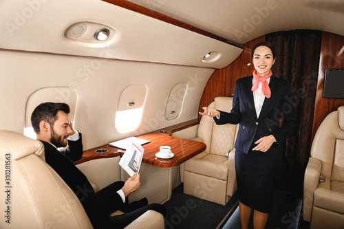 Air hostess and businessman on board the modern private airplane Wallpaper Mural