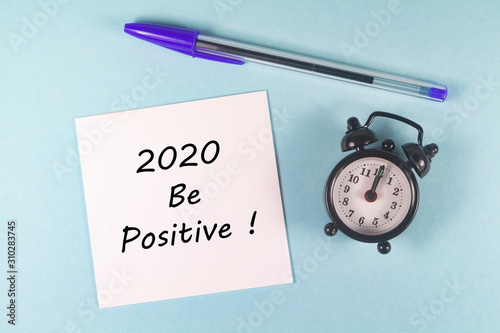 Pen, paper with 2020 be positive and black alarm clock on blue background Wallpaper Mural