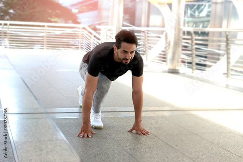 Cuadros en Lienzo Young runner man stretching body before exercise run outdoor, hansom male jogger