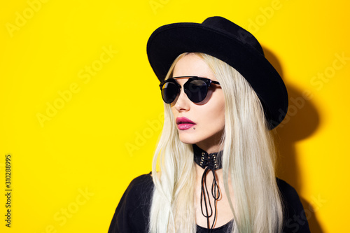 Studio portrait of young fashion blonde hipster girl with pink lips, wearing sunglasses, black hat and choker, isolated on yellow background Wallpaper Mural