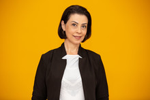 Attractive Middle Aged Woman With Beautiful Smile On Yellow Wall. Pretty Older Business Woman, Successful Confidence.