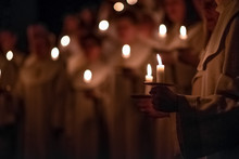 People Are Handling Candles In The Traditionall Religious Habit Dresses In The Church. Celebration Of Lucia Day, Sweden
