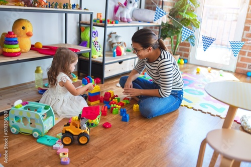 Obraz Beautiful teacher woman and toddler playing with building blocks around lots of toys at kindergarten - fototapety do salonu