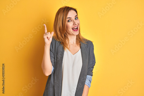 Obraz Redhead caucasian business woman over yellow isolated background pointing finger up with successful idea. Exited and happy. Number one. - fototapety do salonu
