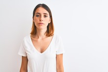 Beautiful Redhead Woman Wearing Casual White T-shirt Over Isolated Background Relaxed With Serious Expression On Face. Simple And Natural Looking At The Camera.