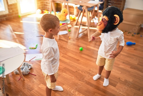 Obraz Adorable blonde twins playing wearing monkey mask around lots of toys at kindergarten - fototapety do salonu