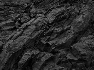 Black rock background. Dark gray stone texture. Black grunge background. Mountain close-up. Distressed backdrop.