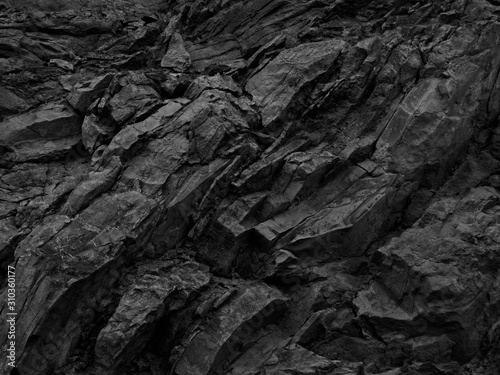 Black rock background. Dark gray stone texture. Black grunge background. Mountain close-up. Distressed backdrop. - 310360177