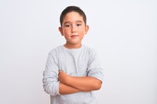 Beautiful Kid Boy Wearing Grey Casual T-shirt Standing Over Isolated White Background With Serious Expression On Face. Simple And Natural Looking At The Camera.