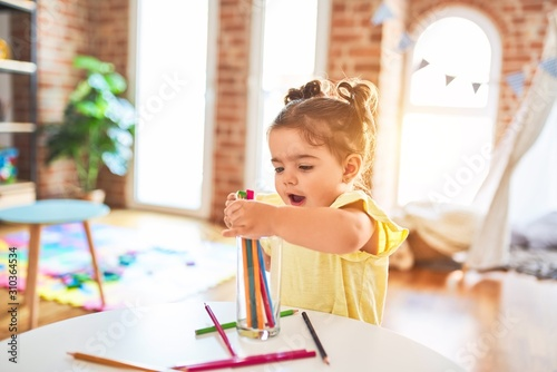 Obraz Beautiful toddler standing holding colored pencils at kindergarten - fototapety do salonu