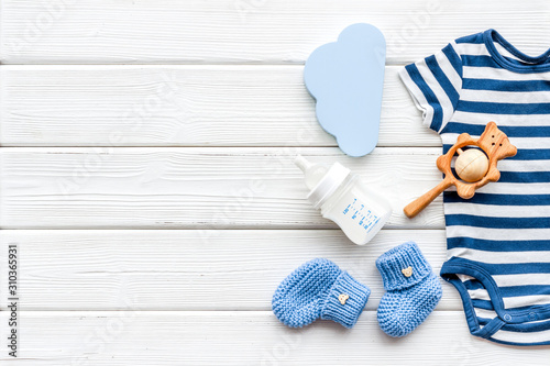 Obraz Newborn baby boy set - blue clothes as bodysuit, booties, toys - on white wooden table top-down frame copy space - fototapety do salonu