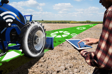 IOT smart industry robot 4.0 agriculture concept.Autonomous tractor working in farm.Smart farming and digital transformation in agriculture.farmer with tablet controls autonomous tractor in farm.