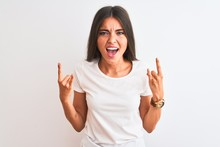 Young Beautiful Woman Wearing Casual T-shirt Standing Over Isolated White Background Shouting With Crazy Expression Doing Rock Symbol With Hands Up. Music Star. Heavy Music Concept.