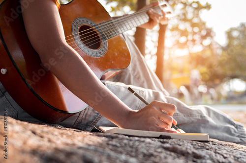 Songwriter writing on notebook with acoustic guitar. Canvas Print