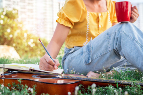Songwriter writing on notebook with acoustic guitar, holding coffee cup Tablou Canvas