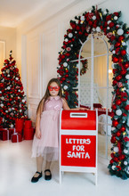 Funny Little Girl In Red Glases Stands Near Mailbox Indoors.
