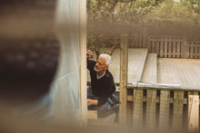Senior Man Repairing Fence