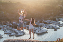 Mother With Daughter Jumping At Sea