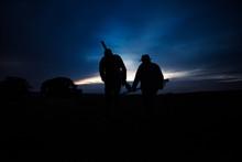 Hunters In Field At Dusk