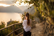 Woman Taking Picture Of Coast