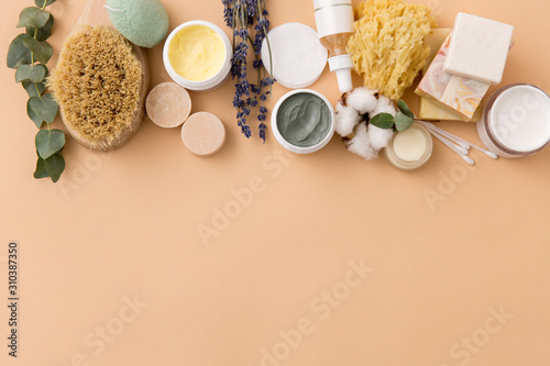 Fototapeta beauty, spa and wellness concept - close up of crafted soap bars, natural bristle wooden brush, body butter with sponge and herbs on beige background obraz na płótnie