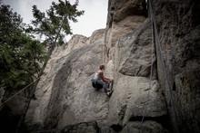 Young Woman Climbing Rock Wall