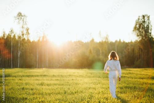 Woman walking in meadow - 310389783